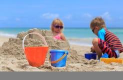 与沙子的孩子戏剧在夏天海滩 库存照片
