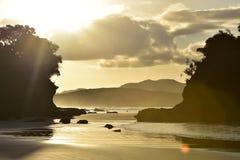 与沙子的海洋在后面光的海滩和岩石 免版税库存照片