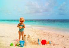 与沙子,在海滩的修造的城堡的逗人喜爱的小女孩戏剧 库存照片