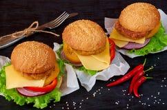 与沙拉三明治、沙拉、洋葱圈、乳酪、蕃茄、辣椒和芝麻的鲜美汉堡在黑背景 图库摄影