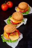 与沙拉三明治、沙拉、洋葱圈、乳酪、蕃茄和辣椒的三个鲜美汉堡在黑背景 免版税库存图片