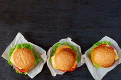 与沙拉三明治、沙拉、洋葱圈、乳酪和蕃茄的三个汉堡在黑背景 传统中东快餐 库存图片