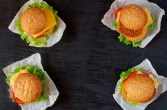 与沙拉三明治、沙拉、洋葱圈、乳酪和蕃茄的四个汉堡在黑背景 经典美国素食者快餐 免版税库存照片