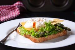 与沙拉叶子、芦笋、乳酪和荷包蛋的敬酒的三明治 免版税图库摄影