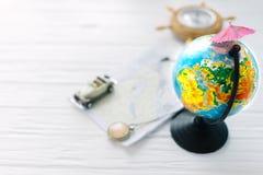 与沙滩伞的地球在木白色背景 免版税库存图片