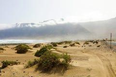 与沙漠沙丘和薄雾的Caleta de Famara风景在背景,兰萨罗特岛,加那利群岛的山 图库摄影