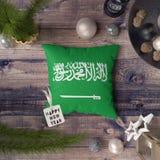 与沙特阿拉伯大型书本和普林西比旗子的新年快乐标记在枕头 在木桌上的圣诞装饰概念与可爱 皇族释放例证