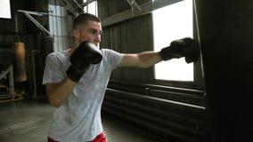 与沙袋的英俊的年轻男性训练在健身房 有效地工作在她的拳打的勤勉拳击手与 股票视频