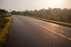 与沥青高速公路路的美丽的太阳上升的天空 图库摄影