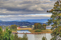 与河、山和cloudscape的黄昏风景 图库摄影