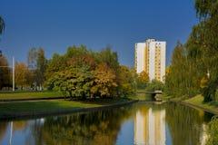 与河、树和房子的城市风景 图库摄影