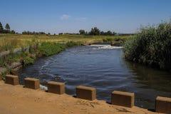 与河、桥梁和测流堰的非洲风景 免版税库存图片