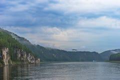 与河、森林、云彩在蓝天和太阳的夏日风景 库存图片