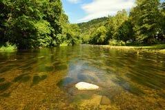 与河、森林、太阳和蓝天的美好的夏天风景 自然本底 免版税库存图片