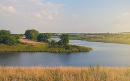 与河、领域、青山和美丽的树的晴朗的夏天风景 免版税库存照片