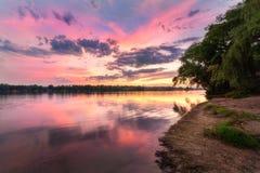 与河和五颜六色的天空的平静的场面与在日落的云彩 图库摄影