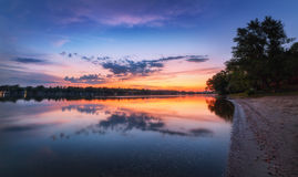 与河和五颜六色的天空的平静的场面与在日落的云彩 免版税图库摄影