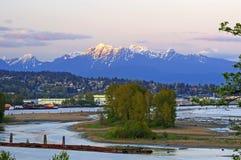 与河的黄昏与红色日落的风景和山点燃在峰顶 库存图片