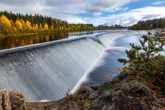 与河水坝和森林的秋天风景 免版税库存图片