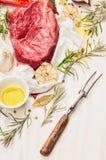 与油、香料、肉叉子和新鲜的调味料的未加工的牛肉肉在白皮书,烹调的准备 免版税库存图片