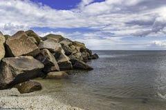与油污染的大岩石在海滩 库存照片