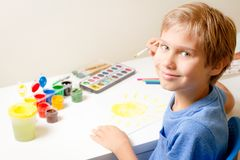 与油漆刷和五颜六色的水彩油漆的愉快的孩子绘画 图库摄影