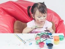 与油漆刷和五颜六色的油漆儿童发育概念的小女孩绘画 图库摄影