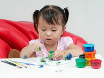 与油漆刷和五颜六色的油漆儿童发育概念的小女孩绘画 免版税库存照片