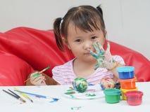 与油漆刷和五颜六色的油漆儿童发育概念的小女孩绘画 免版税库存图片