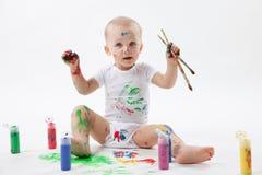 与油漆刷和五颜六色的油漆的逗人喜爱的小的婴孩绘画在白色背景 图库摄影