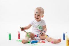 与油漆刷和五颜六色的油漆的逗人喜爱的小的婴孩绘画在白色背景 免版税库存图片