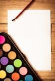 与油漆刷和五颜六色的颜色盒的空的纸在木ta 免版税库存照片
