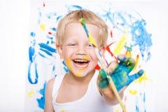 与油漆刷图片的小的杂乱孩子绘画在画架 教育 创造性 学校 幼稚园 在白色b的演播室画象 图库摄影