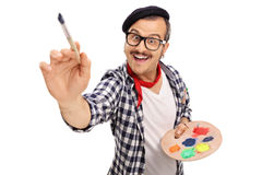 与油漆刷的快乐的年轻艺术家绘画 库存照片