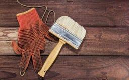 与油漆刷的肮脏的手套在木表上 免版税库存图片