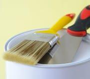 与油漆桶和油灰刀关闭的画笔 免版税库存图片