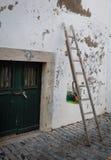 与油漆桶的梯子对有绿色门的老墙壁 库存图片