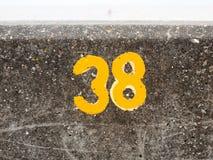 与油漆的一个黄色编号在海滨人行道墙壁Harwich 38上 免版税库存图片