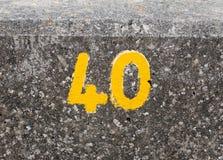 与油漆的一个黄色编号在海滨人行道墙壁Harwich 40上 免版税库存图片