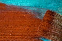 与油漆的刷子在手中 一个人绘一支棕色画笔的蓝色委员会 免版税库存照片