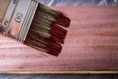 与油漆的刷子在手中 一个人绘一支棕色画笔的蓝色委员会 图库摄影