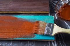 与油漆的刷子在手中 一个人绘一支棕色画笔的蓝色委员会 库存照片