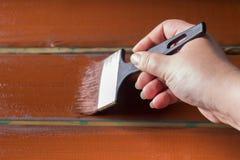 与油漆的刷子在手中 一个人绘一支棕色画笔的蓝色委员会 免版税库存图片