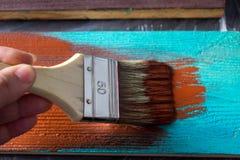 与油漆的刷子在手中 一个人绘一支棕色画笔的蓝色委员会 免版税图库摄影