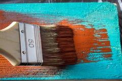 与油漆的刷子在手中 一个人绘一支棕色画笔的蓝色委员会 库存图片