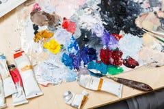 与油漆的艺术家桌,调色板 免版税图库摄影
