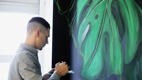 与油漆的街道画艺术家画的分支在sallon的墙壁上 影视素材