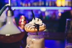 与油炸圈饼的奶昔 牛奶蓝色鸡尾酒胆小鬼在咖啡馆的桌上站立在黑暗的背景 库存照片