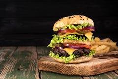 与油煎的土豆菜和牛肉的大水多的汉堡包在黑木rustick背景 被定调子的葡萄酒 免版税库存图片