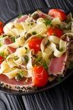 与油煎的金枪鱼排、蕃茄和雀跃clos的意大利细面条面团 图库摄影